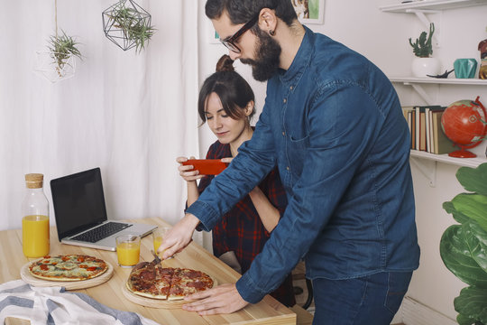 Young couple eating pizza and drinking juice for lunch, woman taking pictures with smart phone