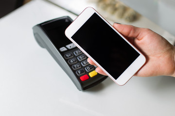 Woman hand with mobile phone using NFC (near field communication) technology for payment in the shop.
