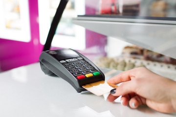Female hand with silver bank card using the pos-terminal for payment.