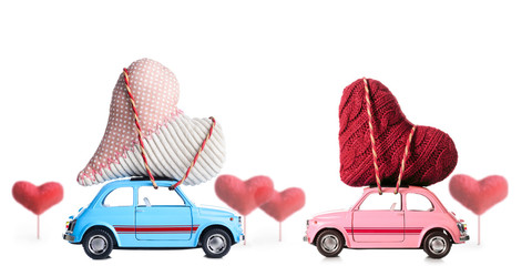 Couple of retro toy cars delivering craft hearts for Valentine's day on white background