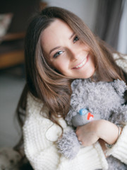 woman holding teddy bear and smiling