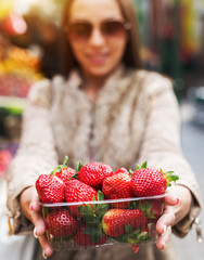 Woman is holding box with strawberries.