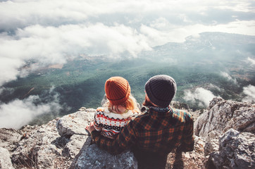 Couple Man and Woman sitting hugging on cliff enjoying mountains and clouds landscape Love and Travel happy emotions Lifestyle concept. Young family traveling active adventure vacations