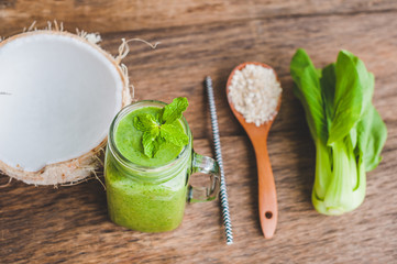 Mason jar mugs filled with green spinach, banana and coconut milk health smoothie with with a spoon of oatmeal on wooden rustic table