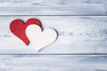 Red and white Valentine hearts over wooden background
