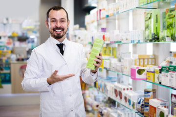 Smiling man pharmacist showing right drug