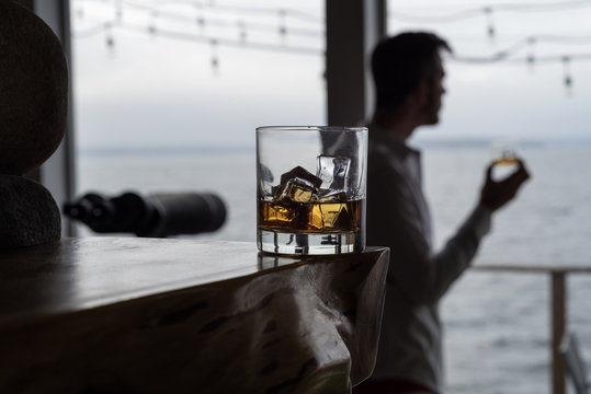 Scotch  on the Rocks with man in background enjoying window view.