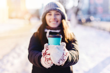 Young happy stylish woman drinking coffee to go outdoors. Selective focus on hands.