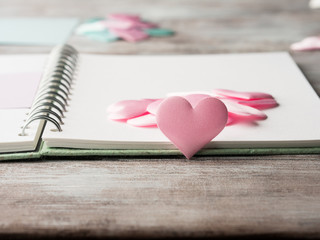 Pink hearts on notebook textured wooden table. Valentine's mother day or baby birthday card