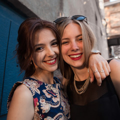 Two beautiful girl hugging each other,looking at camera.Closeup photo of strong true friendship of beautiful girls.Outdoor lifestyle portrait of two best friends,having fun together, joy and happiness