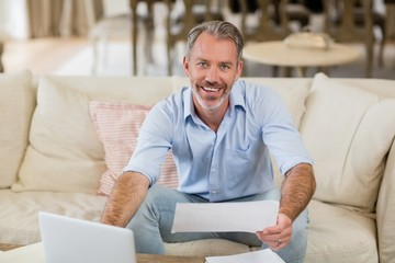 Happy man holding a bill in living room