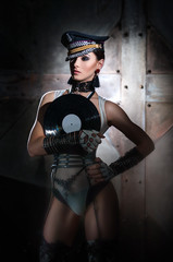 DJ on a dark background with cap and vinyl records in hand