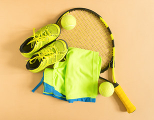 Sport, fitness, tennis, healthy lifestyle, sport stuff. Tennis racket, lime trainers, tennis ball, lime athletic shorts. Flat lay, top view.