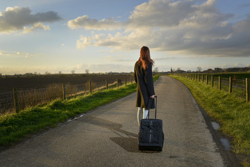 runaway girl standing with her suitcase on the road