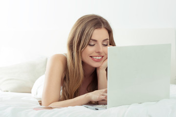Happy woman working on laptop in bed.