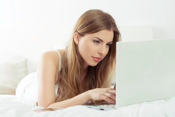 Young woman focus on work on laptop in bed.