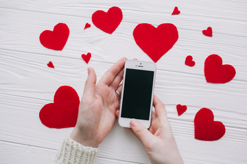 valentines day.female holding smat phone on white wooden background with red hearts