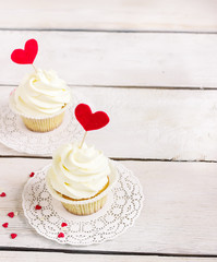 Cupcakes with red hearts for St. Valentines Day.White wooden background.
