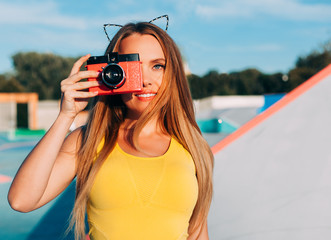 Close up Portrait of beautiful woman with retro hipster camera having fun in skatepark. Warm sunny summer evening. Close up. Outdoor.