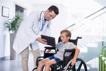 Smiling doctor showing digital tablet to disable boy