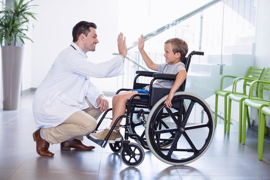 Doctor giving high five to disable boy