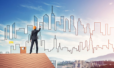 Man architect draw silhouette of modern city on blue sky. Mixed