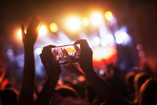 Crowd at concert recording atmosphere with their smart phones.