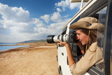 Girl taking photo from the window of safari jeep