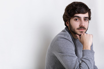 Sideways portrait of young hipster having dark beard with moustache big dark eyes, thick eyebrows and fashionable hairstyle holding his hand on his chin having clever serious expression.