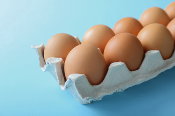 Raw eggs in package on blue background