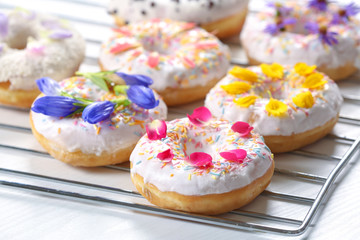 Delicious donuts and flowers on baking rack and white background, closeup