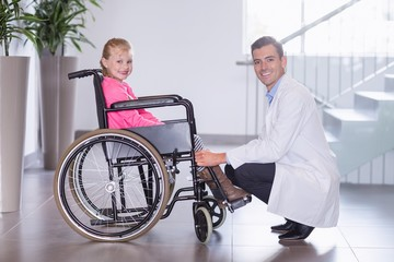 Portrait of smiling doctor and disable girl