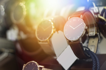 Beautiful brown leather watch in front of other watches. Lens flare in background.