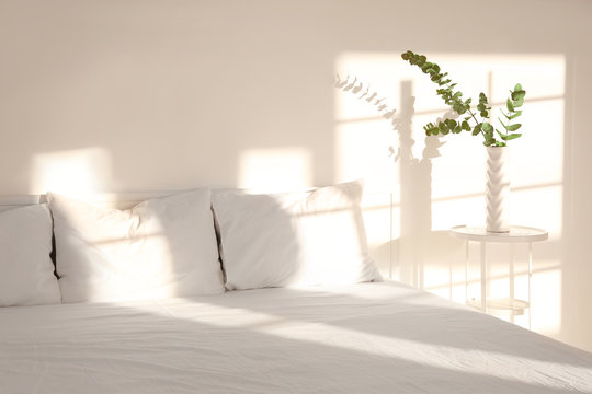 White interior of modern bedroom with cozy double bed