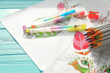 Colouring pictures, pencils and pens on wooden table, closeup