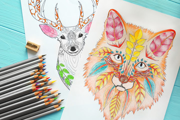 Colouring pictures and pencils on wooden table, closeup