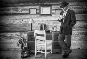 horizontal black and white image of a caucasian man in a  business suit and hat standing by his desk holding a cup of coffee.