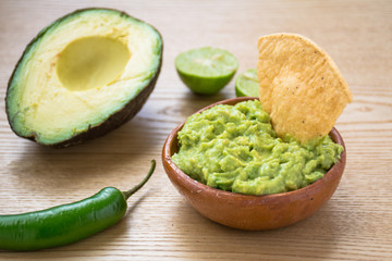 Guacamole dip and tortilla chips on wooden surface