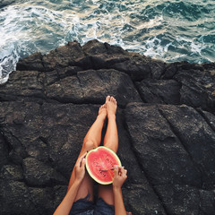 Woman eat watermelon on beach. Stone edge of cliff