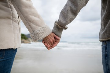 Couple standing with holding hands on the beach