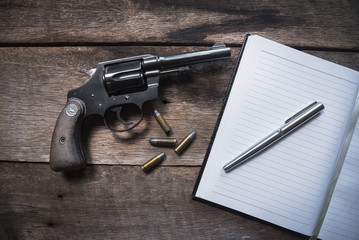 Gun and ammunition and blank notebook on wooden table. top view