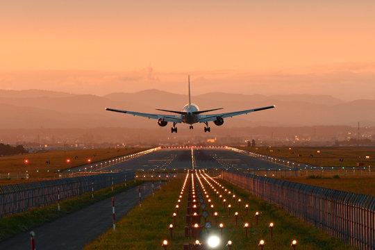 夕陽に向って着陸する飛行機