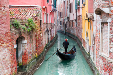 Venetian gondolier punting gondola through green canal waters of Venice Italy Fototapete