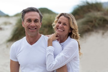 Smiling mature couple standing together on the beach