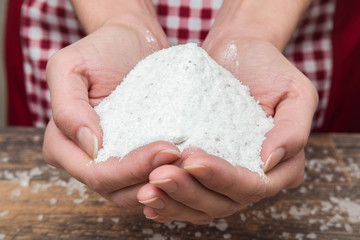 White salt in the hands on the table in the kitchen.