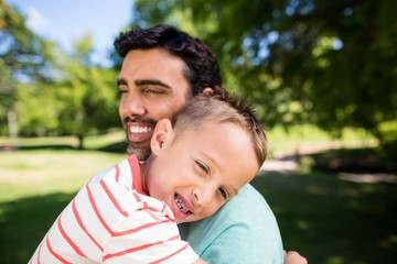 Son smiling while embracing his father in park