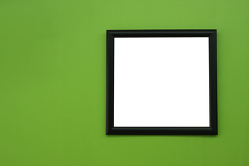 Black blank picture frame on greenery color paint wall backgroun