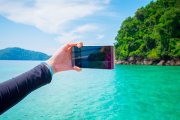 Female hand holding smartphone taking picture of Beautiful sea,i