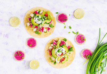 Healthy mexican corn tacos with boiled chicken breast, avocado and watermelon radish and yogurt dressing. Flat lay. Top view