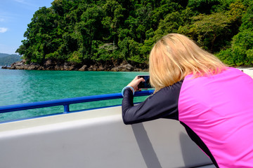 Female   taking picture of Beautiful sea,island and blue sky wit